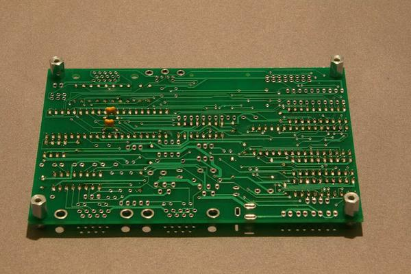 A PCB from solder side with two capacitors mounted.