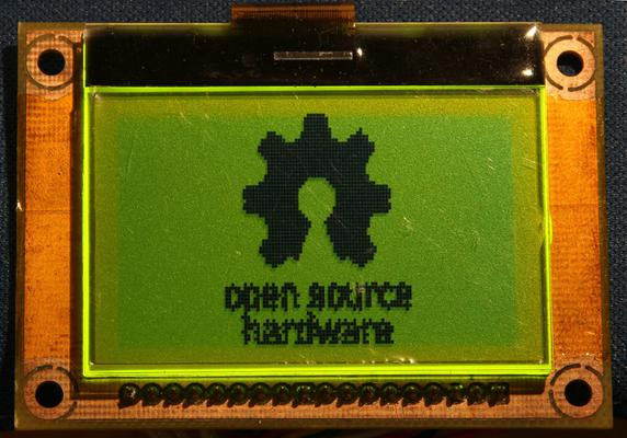 A picture of a graphical LCD showing the Open Source Hardware logo