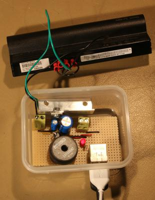 A circuit in a small plastic box connected to two USB leads and a small laptop battery