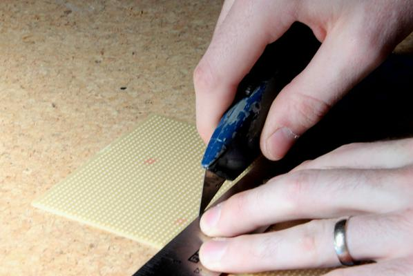 Use a steel ruler, a good knife and a cutting mat.  Be careful cutting stripboard, it's quite hard so easy for the knife to slip.